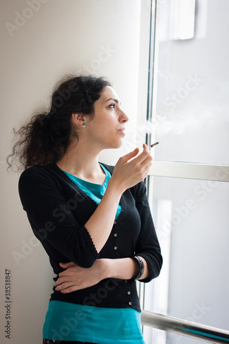 Young woman smoking indoors
