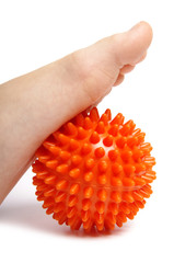 Childs foot with spiny plastic orange massage ball on white back