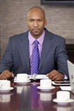 African American Businessman Sitting in Office Boardroom