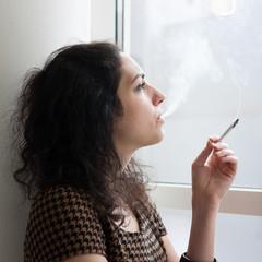 Young woman smoking indoors