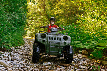 A little boy wearing a helmet riding a quad bike