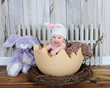 adorable baby in bunny hat sitting in giant easter egg