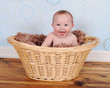 sweet baby sitting with big smile in wicker basket