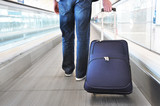 Traveler with a bag on the speedwalk . poster