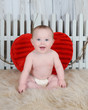 sweet baby boy sitting with large red heart