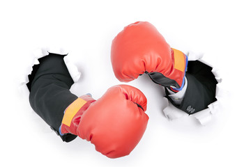 Businessman's hand in fight position wearing boxing gloves