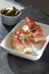 Ham Crostini with cornichons on slate