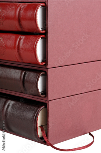 Stack of red and brown leather diaries in hard cover boxes