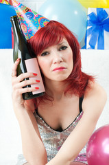 Young party woman with hangover holding a wine bottle