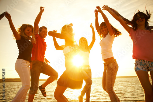 happy young people dancing at the beach