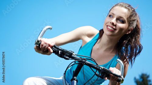 woman with bike under blue skies