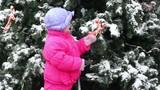 Little girl shake bow ribbon on Christmas tree