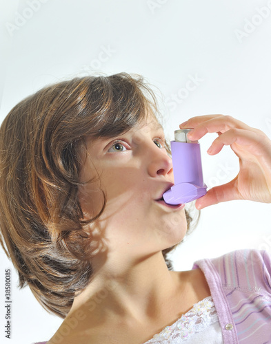 girl using an inhaler for asthma