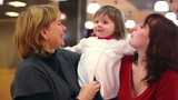 Grandmother and mother kiss little girl inside cafeteria