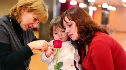 Two females and little girl look on rose