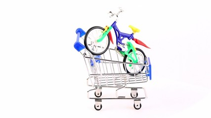 Toy bicycle is in shopping cart, composition rotates
