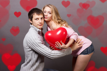 Portrait of two young people holding heart-shaped balloon