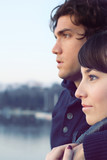 Romantic couple staring to horizon embraced