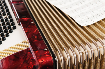 Red accordion and sheet music, close up