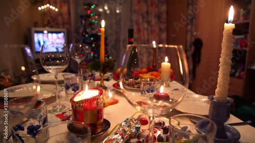 Candles and glasses on decorated christmas dining table