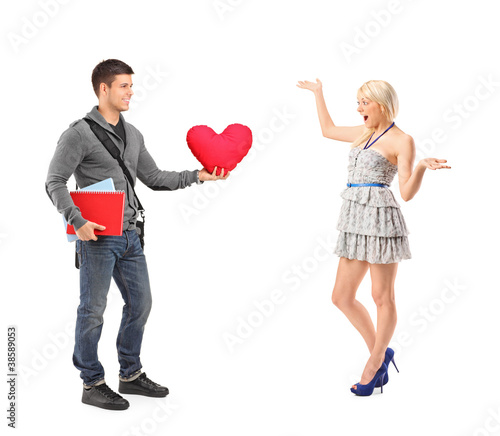 Boyfriend standing with a pillow and a girlfriend extending her