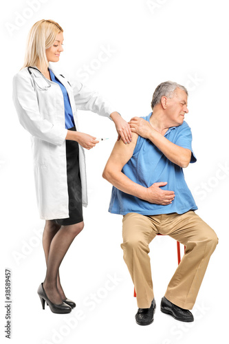 Female doctor applying a syringe to an elderly man