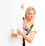 German girl holding a pint of beer behind a blank billboard