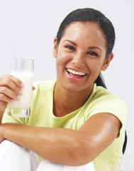 Mujer latina bebiendo un vaso de leche.