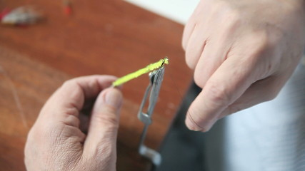 man ties an artificial fishing fly