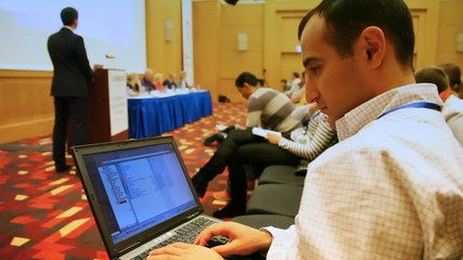 Elnur Amikishiyev looks at conferences in laptop
