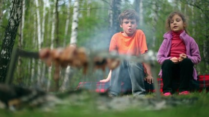 Boy and girl sit and talk, meat cooking on embers