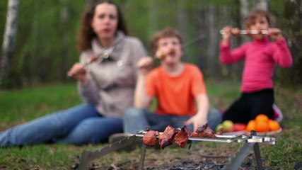 Mom and two kids, sit on grass cover by plaid and eats kebab