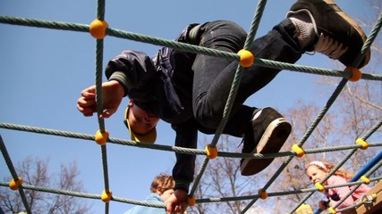 Kids climb on rope lattice at playground, view from below