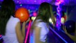 Three girls stand with bowling balls and then throw it