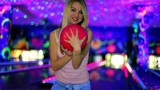 girl shakes her body and then takes bowling ball in club