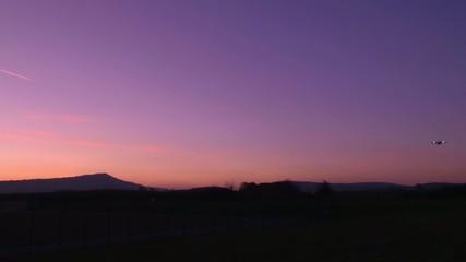 Flugzeug landet vor vom Abendrot gefärbtem Himmel