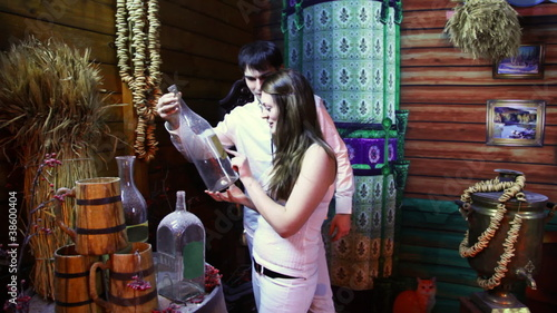couple stands in ancient wooden house and sees old bottles