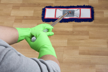 cleaner is mopping wooden parquet floor