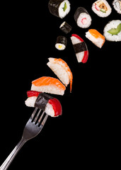 Sushi pieces falling on fork, isolated on black background