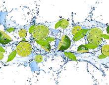Świeże limes w plusk wody, na białym tle