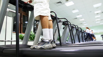 man stand at treadmill in gym, he turn on and begins run