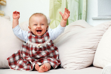 laughing baby with hands up
