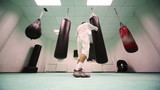 man in gloves punches punchbag at large boxing gym