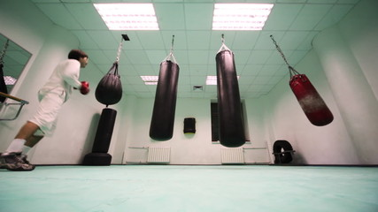 man jumps and punches on punching bag at boxing gym, part3