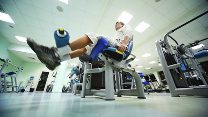 man does exercise for legs while sitting on exerciser in gym