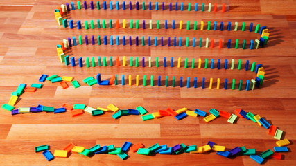 many colored dominoes built zigzag on parquet