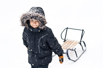 Young boy in winter suit pulling sledges