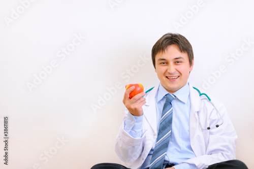 Smiling medical doctor sitting on floor and holding apple in han