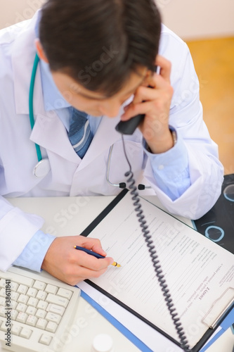 Medical doctor speaking phone and notes in clipboard. Top view
