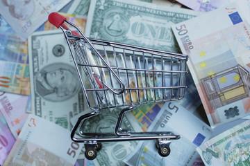 Einkaufswagen mit Banknoten Euro, Dollar, Franken, Pfund